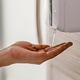 A motion-activated hand sanitiser dispenser in use.